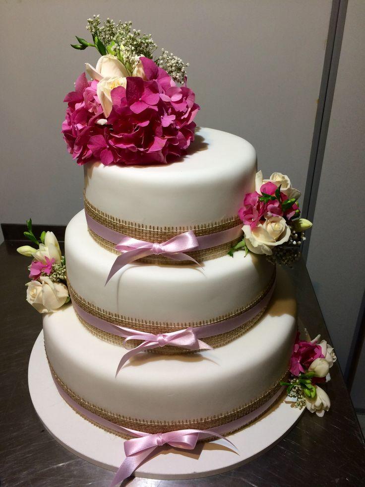 Třípatrový svatební dort obalený fondánem, dozdobený jutovými a saténovými stuhami a čerstvými květinami
