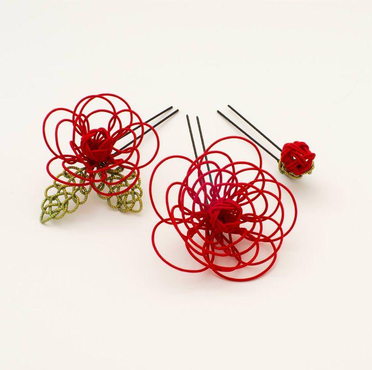 ミニ薔薇の水引細工をあしらった髪飾りです。 大きなお花と、葉のついた中サイズのお花、つぼみの3種類がセットになっていますので、一つだけ付けたり、三つ全て付けたりとアレンジを楽しめます。