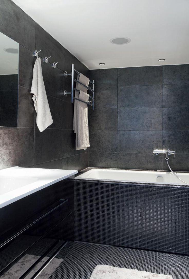 Kylpyhuone on dramaattisen tummasävyinen. Seinälaatat valittiin Pukkilasta ja lattian mosaikkilaatat Laattapisteestä. Kahden hengen amme on sveitsiläisen Laufenin. Tanskalaisen Dansanin kylpyhuonekalusteet ovat Laattapisteestä. Allas Dansanin Luna-mallistoon kuuluva Kantate, hanat ovat Hansgrohen, pesukone ja kuivausrumpu Boschin | Papukaija opetti minimalistiksi | Koti ja keittiö