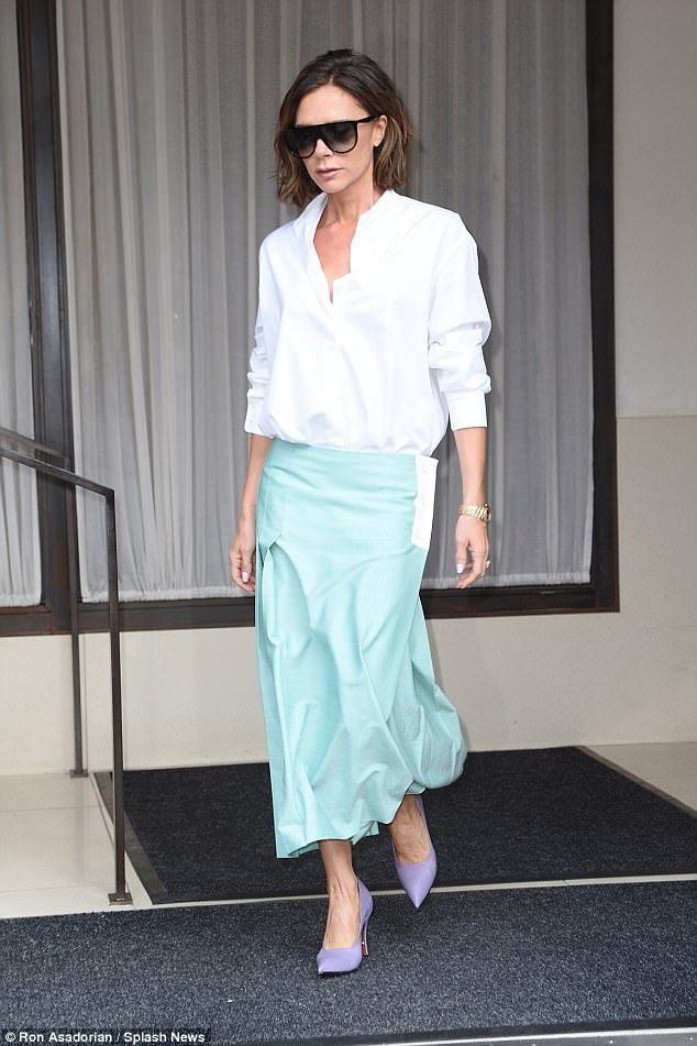 Fashionista: Victoria Beckham, 43, couldn't help but put on another sartorial display in her signature crisp white shirt and midi-skirt as she emerged from her New York hotel on Monday