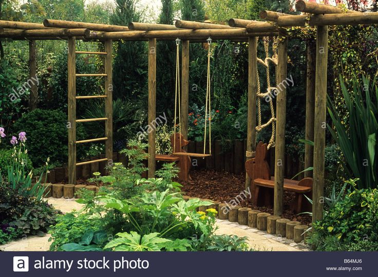 child friendly wooden climbing apparatus in corner of garden Stock Photo                                                                                                                                                                                 More