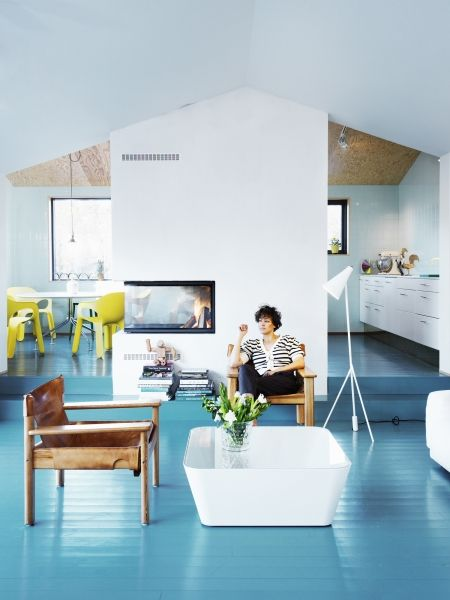 blue painted floor, vaulted ceiling, white walls, cocktail table, armchair, fireplace, floor lamp #home #midcenturymodern