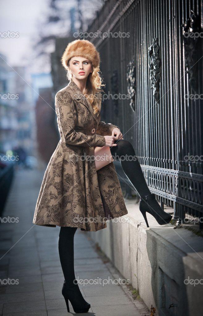 魅力的なエレガントなブロンド若い女性都市のファッションのショットでロシアの影響と服を身に着けています。長い脚と毛皮帽通りでポーズ美しいファッショナブルな少女 - ストック画像: 39955913