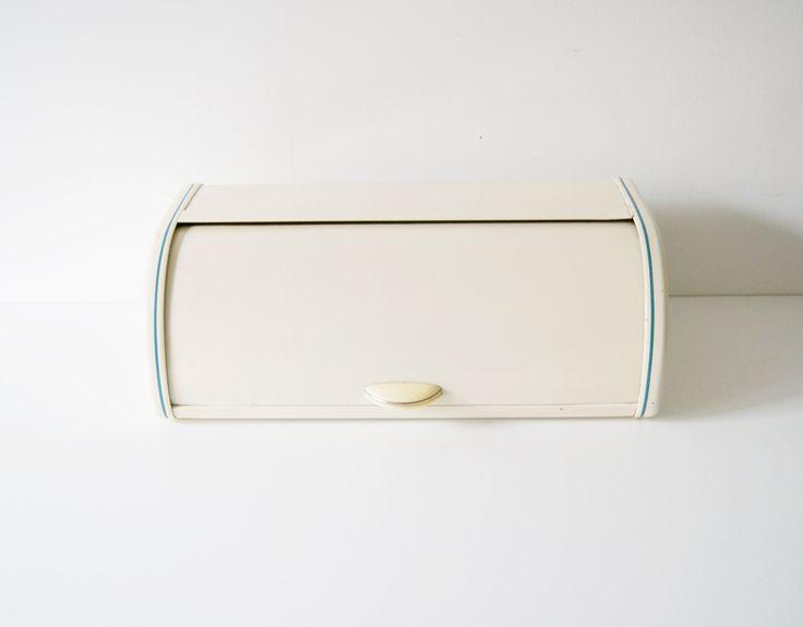 Iconische metalen brood vak glazuur wit/beige met blauwe kant strepen en typische greep van de tijd. Een geweldige unieke voor opslag van brood en toast. Zijde ventilatieopeningen om een levering van zuurstof. Allgeimein zichtbaar, gelieve nota fotos ouderdom en slijtage.  Afmetingen: Hoogte 16 cm Lengte 47 cm Breedte 24 cm  Art. Nr. 2567