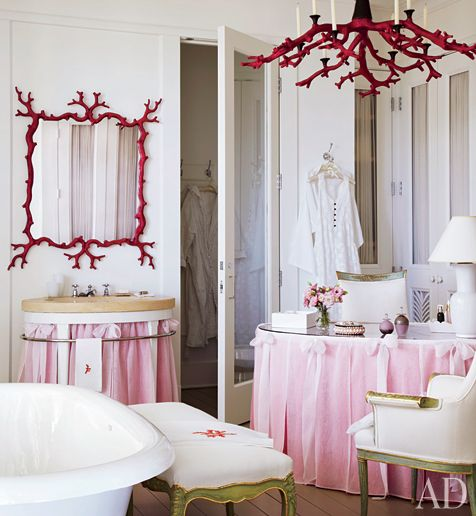 Bowed organza skirts the sink vanity and dressing table in the master bath; the faux-coral mirror and chandelier were commissioned from British artist Oriel Harwood.