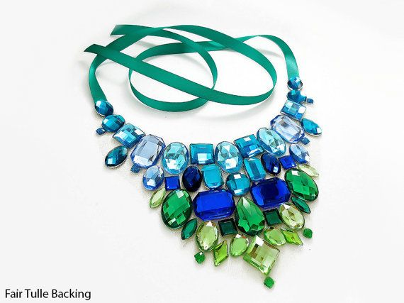 This mermaid inspired statement bib necklace is made with blue and green rhinestones to create a ombre effect! This was designed and is hand made to order by me.  I set each rhinestone onto a sheer fabric base (it is best to select a fabric that matches your skin tone. See my photos of the fabric examples!), and a satin ribbon makes this piece completely adjustable. Felt circles line the back for added comfort when worn.  ► Materials used: Acrylic rhinestones, satin ribbon, felt and sheer…