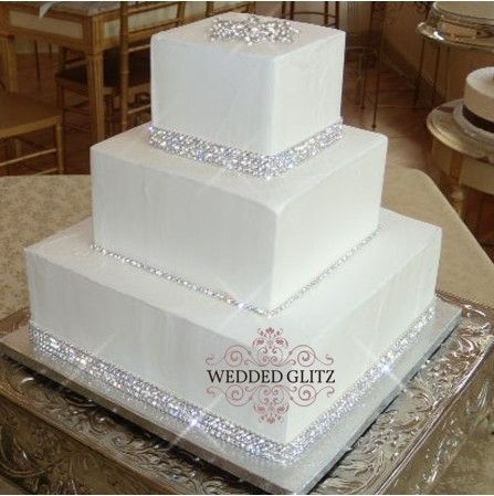 A 3-tier white fondant wedding cake with rhinestone banding at the base of each…