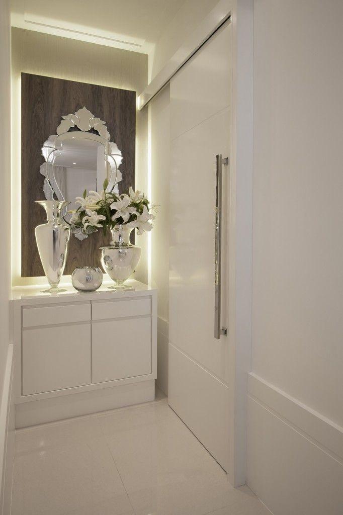 Na passagem para a área íntima, o branco predominante é destacado pelo espelho veneziano e pelos objetos