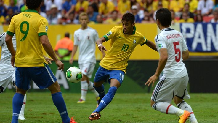 Brazil's forward Neymar kicks the ball to score against Japan during their FIFA Confederations Cup Brazil 2013 Group A football match, at the National Stadium in Brasilia on June 15, 2013.  AFP PHOTO / YASUYOSHI CHIBA