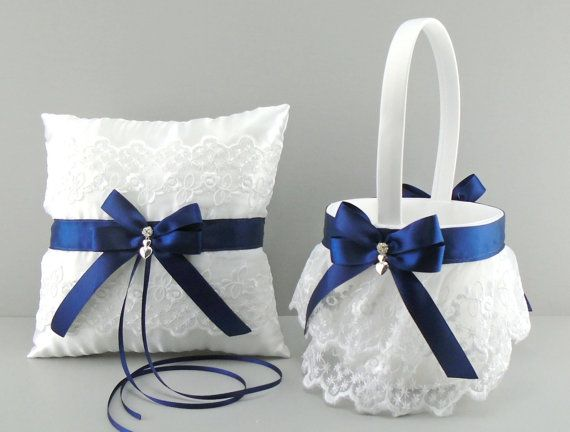 Customize your wedding with this beautiful Navy Blue on white or ivory satin and embroidered lace flower girl basket and ring bearer pillow set.  The ivory or white satin basket features two tiered rows of a pretty ruffled embroidered lace. The top of the basket is trimmed in ribbon, with double loop bows that are embellished with a double heart silver plated charm and a delicate sparkling rhinestone bead.  The basket measures approximately 9.5 from the top of the handle to the base of the…