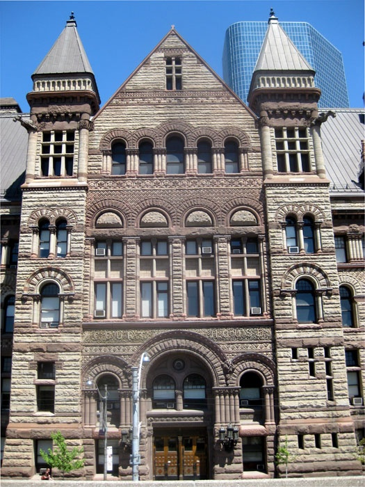 Old City Hall, Queen West at Bay Street, was the largest building in TORONTO when it opened in 1899. Architect E. J. Lennox added many grotesque and comical gargoyles and faces to the facade – including his own. The building is presently used as a court house, and it may soon become a city museum.    We nearly lost this building back in the sixties. Plans were afoot to keep the tower, tear down the rest, and put up some glass-covered office buildings. What ever were they thinking?