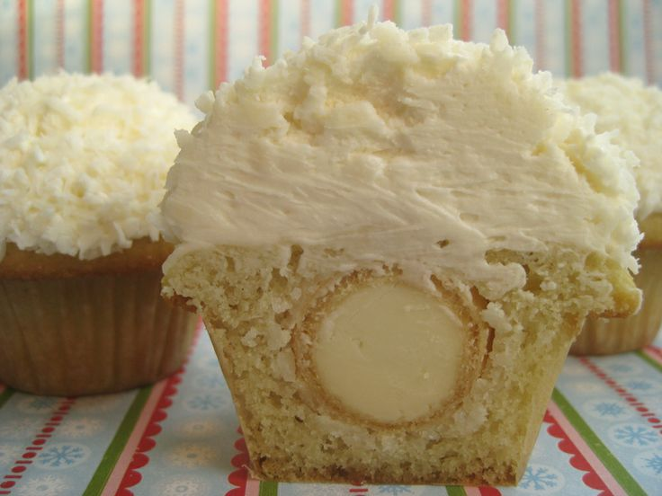 oh coconut heaven.  Coconut Raffaello candy balls in mini vanilla cupcakes, and topped with a mound of vanilla buttercream and more coconut!  From bake it in a cake, a cool baking site!