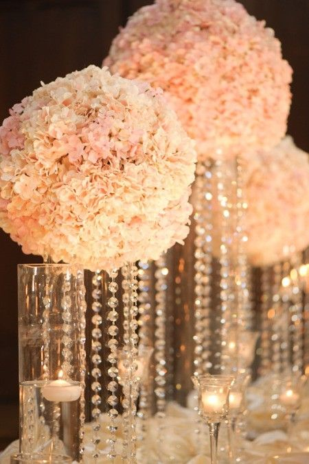 gorgeous white carnation ball and crystal centerpieces with glow sticks under pearls in the vase to make it glowww! this is going to be soooo rad!!