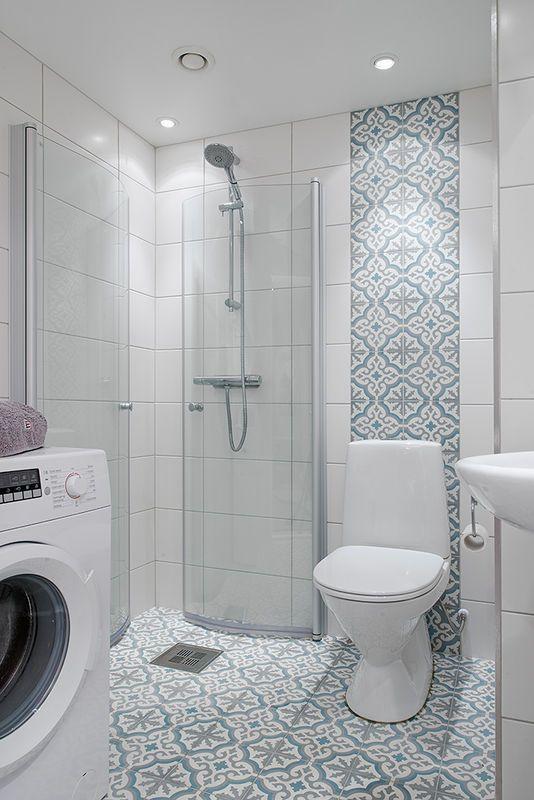 Ściany tej łazienki wyłożono białą glazurą. W linii wc ścianę zdobi pas wzorzystych kafli glazury w tonacji błękitnej. Takie same kafle ułożono również na podłodze. Rozwiązanie zdobi wnętrze, ożywia je oraz powiększa optycznie.