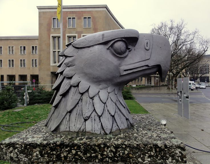 The Eagle Head by Wilhelm Lemke in 1940. Based on a design by Ernst Sagebiel. It was part of a 4,5 meter large bird sculpture which stood on top of the the Tempelhof building but was removed after World War II in 1962 to make room for a radar. The head became part of the collection of the museum of the Military Academy in West Point. In 1984 is was placed where it is now at Eagle Square (Platz der Luftbrücke) in front of the Tempelhof entrance.