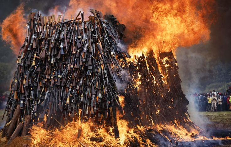 A pile of 5,250 illegal weapons are burned by Kenyan police in Ngong, near Nairobi, in Kenya, 2016 - by Ben Curtis, UK