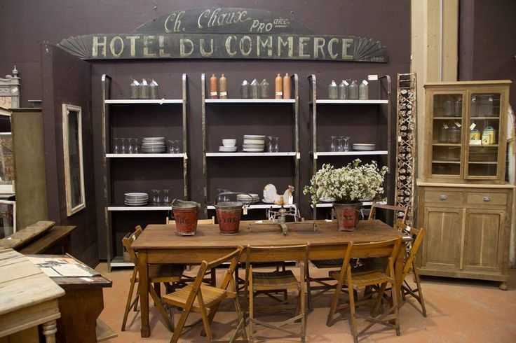 Antique French oak signage, vintage metal shelving units, antique French table and vintage English flip up chairs.