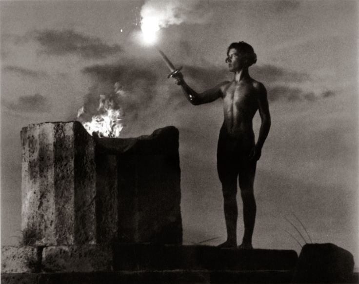 A man torching the Olympic flame, Berlin 1936, pic by Leni Riefenstahl.   The Olympic flame is a symbol of the Olympic Games. Commemorating the theft of fire from the Greek god Zeus by Prometheus, its origins lie in ancient Greece, where a fire was kept burning throughout the celebration of the ancient Olympics.