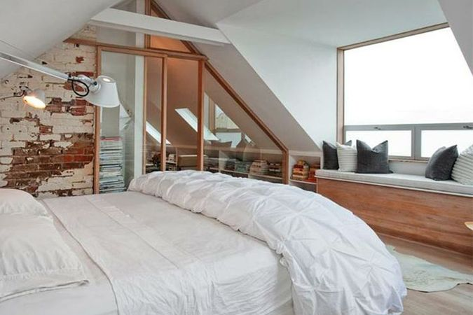 Witte zolderkamer met bakstenen muur - erker raam