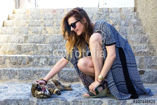 Cheerful young girl stroking a lovely yawning cat on the stairs