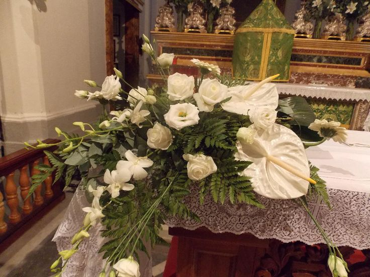 Two elegant flower arrangements  in white Anthuriums, Roses and Austoma against green fern foliage are placed on each end of the Altar.
