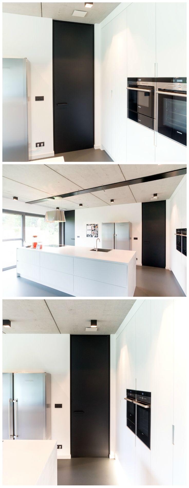 Zwarte deuren op maat van Anyway Doors. De binnendeuren zijn van vloer tot plafond uitgevoerd met een minimalistische blokomlijsting. De unieke sluiting van Anyway laat toe de deur in 1 of beide richtingen te openen. De onzichtbare scharnieren zijn van links naar rechts te verplaatsen om een optimale flexibiliteit te garanderen.
