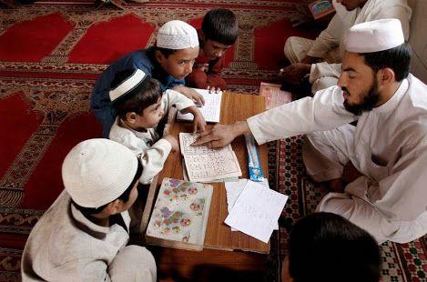 Crianças afegãs se reunem em torno de seu professor para ler versículos do Alcorão, na sua madrassa (escola) , durante o mês de jejum sagrado muçulmano do Ramadã em Jalalabad leste de Cabul, no Afeganistão. AP / Rahmat Gul