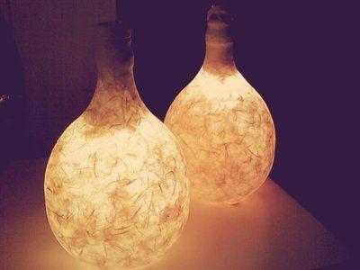Coppia di lampade da comodino o da tavolo ricavate da due damigiane originali.  La loro particolarità è di essere color avorio chiaro da spente per adattarsi ad ogni ambiente e di emanare una luce calda e soffusa quando sono accese.  Totalmente fatte a mano e curate in ogni dettaglio.