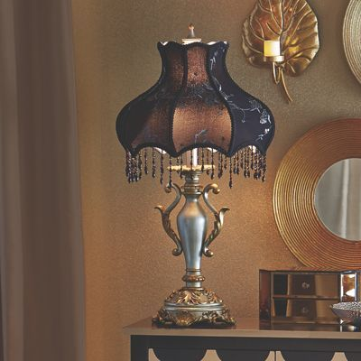 This table lamps shapely base and shade lend a touch of elegance beaded fringe on fabric shade