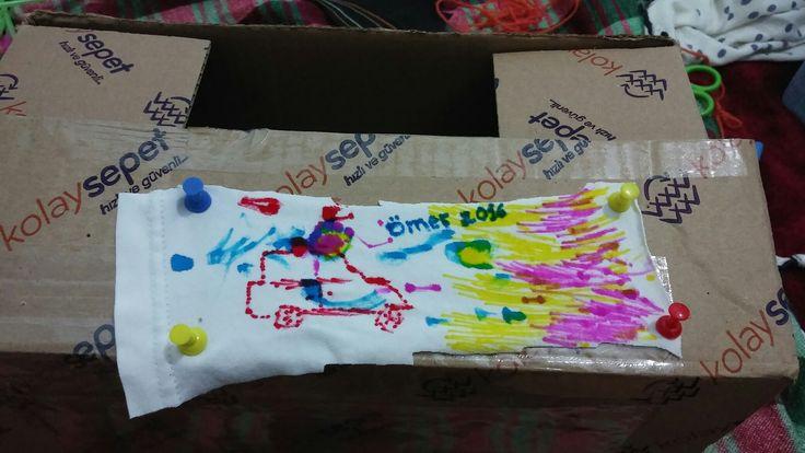 Karton kutu,  keçeli kalemler,   bir parça kumaş ve raptiye ile boyama tahtası