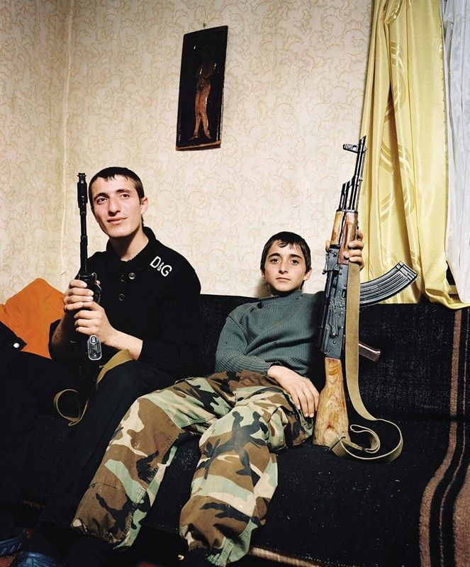 Two brothers pose proudly with Kalashnikovs on the sofa in their grandfather's house. They live in a remote mountainous region on the border between Abkhazia and Georgia. Kodori, Abkhazia, 2009
