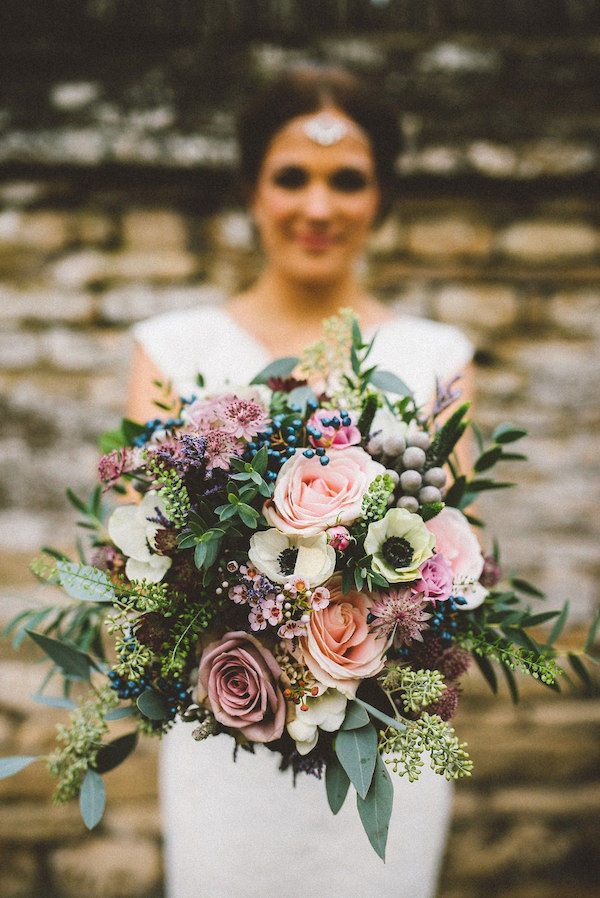 Fall Wedding Bouquet: Use lighter colors like pinks, lilacs, peaches, and lime greens to create fall wedding bouquets. The light colors can soften an autumn wedding and create a beautiful layer of fresh floral romance. The blush roses, anemones, blue berries, eucalyptus and subtle green succulents make this bridal bouquet so magical for a boho bride.