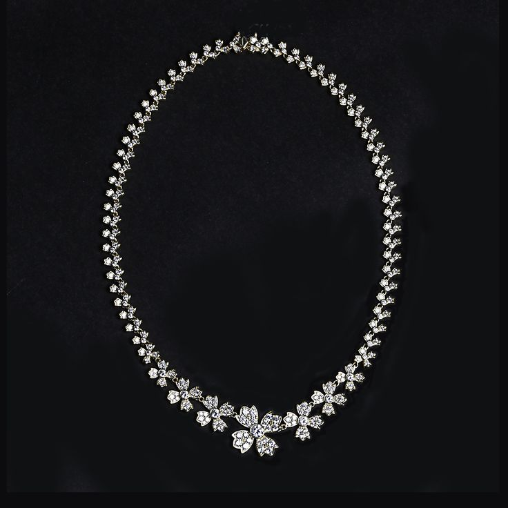 """This stunning piece showcases graduating floral accents that are set with over 200 cubic zirconia stones in sterling silver with vermeil plating and measures at 18""""."""