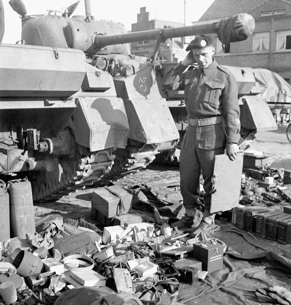 Technical Quartermaster O.T. Hanson of the Calgary Regiment checking tank parts as the regiment re-equips with Sherman Vc Firefly tanks, Dottignies, Belgium, March 22nd 1945.