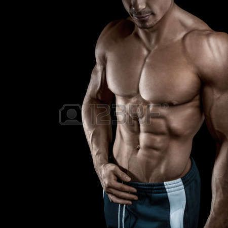 shirtless: Muscular and fit young bodybuilder fitness male model posing over black background. Studio shot on black background.