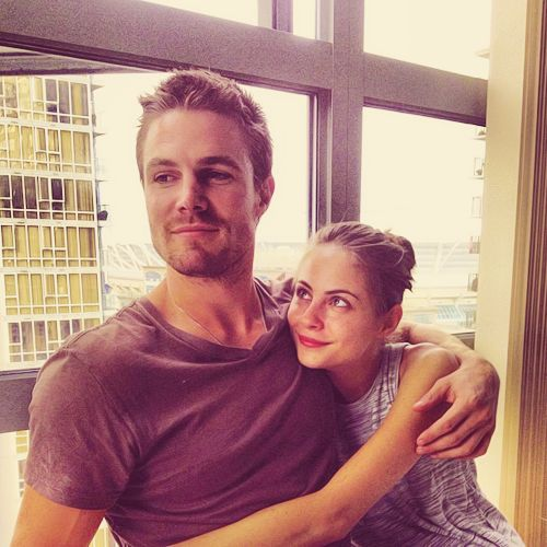 Stephen Amell (Oliver Queen) and Willa Holland (Thea Queen) on the set of Arrow.