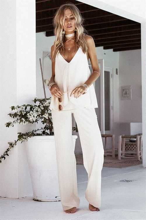 All class in the Ribbed Gia Pantsuit, made from a slightly stretchy ribbed fabric in a cream hue. It is a long wide leg jumpsuit and features a V neckline, split overlay and rope strap detailing. Complete the look with tan slides and gold accessories. By Sabo Skirt.