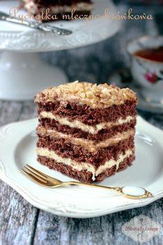 Przepyszne ciasto, któremu nie sposób się oprzeć. Kakawy biszkopt przełożony masą kajmakową, kremem na bazie mleka w proszku i domowym dżemem śliwkowym, który z powodzeniem można zastąpić powidłami śliwkowymi lub konfiturą z czarnej porzeczki.