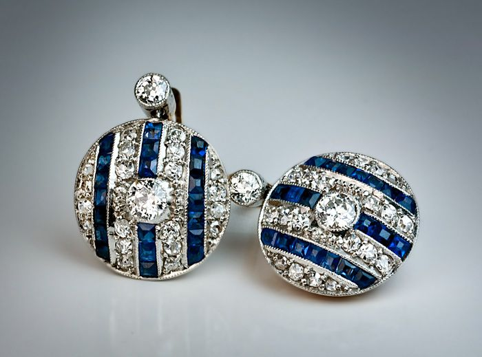 Vintage Art Deco Diamond and Sapphire Earrings, Portuguese, 1920s/1930s. A pair of finely crafted disc-shaped platinum-topped 19K gold earrings, each earring is centered with a sparkling old European cut diamond in a milgrain setting. The background is designed with three vertical rows of channel-set calibre-cut blue sapphires and four rows of bright white single and rose cut diamonds.