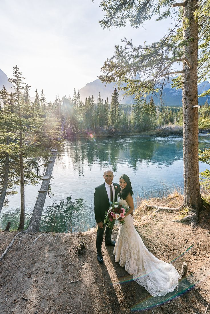 Beautiful fall wedding in Canmore, bride and groom near the river. Photo @oneedition   Canmore Wedding Flowers www.flowersbyjanie.com