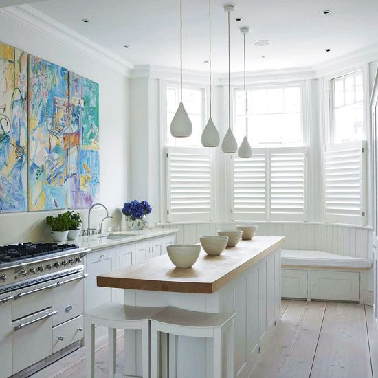Small kitchen with white walls, wood flooring, white shutters, white cabinetry, white island unit and white pendant lighting