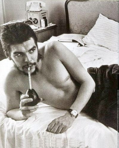 Che Guevara. hair and beard appear to be self cut. jeans + watch + what appears to be a hotel room.