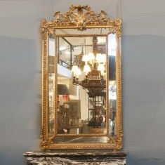 FRENCH GILT CUSHION MIRROR C1860 THE BEADED INNER FRAME RAISED BY ACANTHUS LEAVES WITHIN A EGG AND DART FRAME WITH A CROWNING SPRAY SUPPORTED BY FOLIATE SCROLLES ORIGINAL GILT AND WATER GILT HIGHLIGHTS FRAME THE BEVELLED MERCURY PLATES H1750 L1020 D175