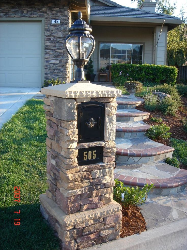 A mailbox with a light on the top, covered with culture stone