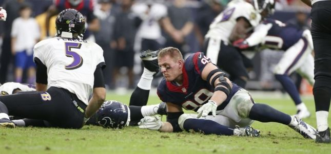 Houston Texans defensive end J.J. Watt (99) looses his helmet and sustains an injury to his nose after tackling Baltimore Ravens quarterback Joe Flacco (5) during the four quarter of an NFL game at NRG Stadium, Sunday, Dec. 21, 2014, in Houston. ( Karen Warren / Houston Chronicle  )
