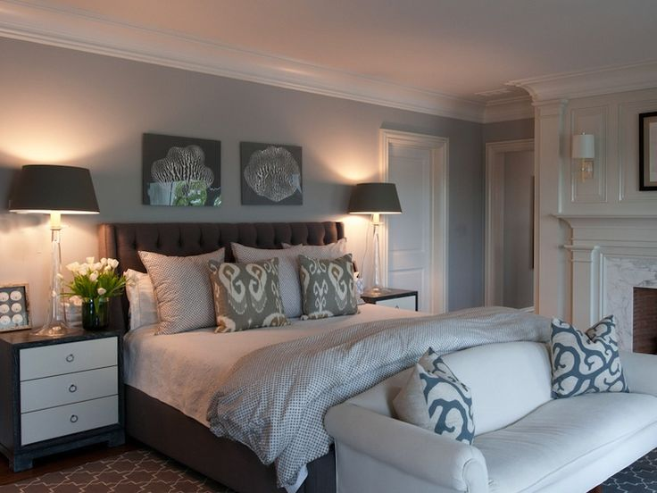 Chic gray bedroom with gray walls framing dark gray tufted headboard and Kravet Bansuri Fabric Slate pillows. Dark gray tufted wingback headboard. Madeline Weinrib Platinum Brooke Rug is tucked under bed whilst white camelback sofa with white and blue coral pillows is placed at foot of bed. Master bedroom features glossy cream fireplace mantel and fireplace marble surround and brick firebox.