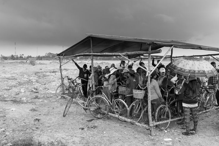 John Vink -  Cambodia. Lvear (Kompong Speu). 21/03/2014: Workers from Gartha International on a week-long strike for various demands, ranging from allowances for food and transportation, to issues with the management, take shelter from the rain under the bicycle parking near the factory gate.