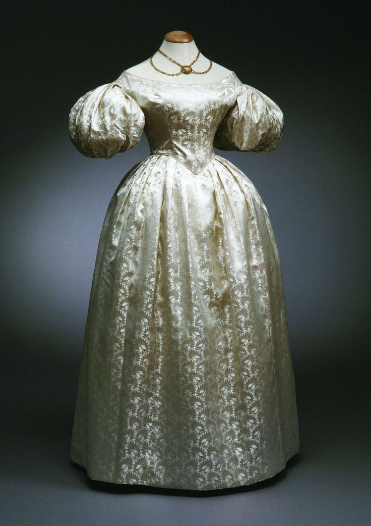 Date     1830 - 1835      Soie, robe de bal pour la mariée I  Satin de soie damassé blanc nacré à motifs de fleurs et feuilles stylisées. Corsage baleiné en pointe devant, décolleté bateau, manches courtes bouffantes. Jupe ronde à plis plats et