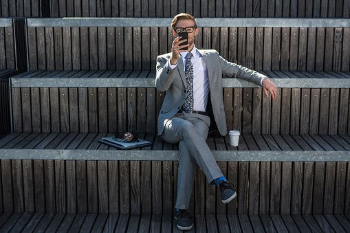 Cool young businessman reading smartphone on city stair