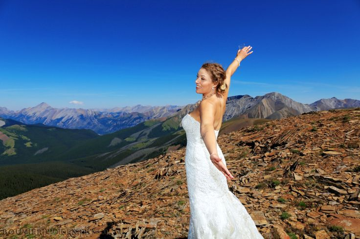 Beautiful bride on top of mountain in Camore, Alberta holding a glass of champagne. Summer heli-wedding. Canmore Alberta wedding.